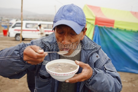 senior man eating a bowl of