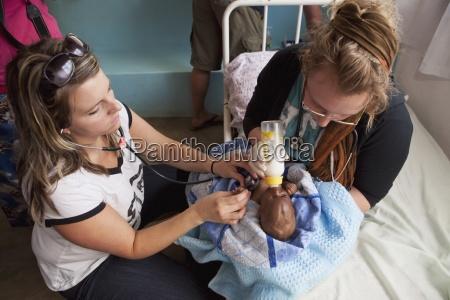 krankenschwestern die sich um ein kleinkind