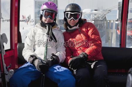 zwei skifahrer fahren mit einer gondelbahn