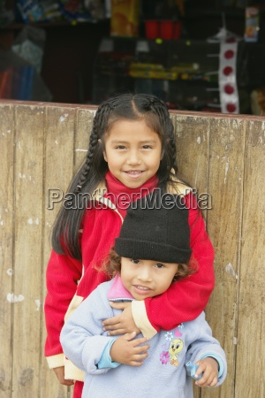young girl embracing younger child lima