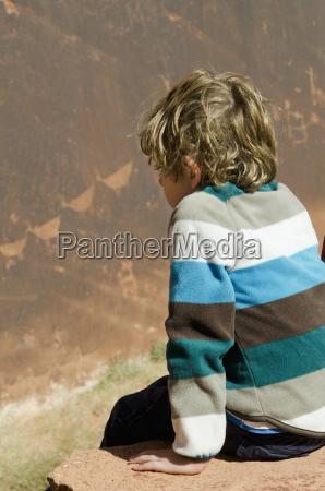 a boy sits on the edge