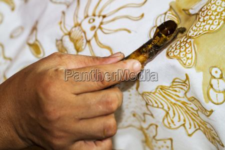 hand of a craftswoman drawing intricate