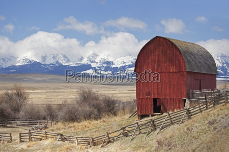 red barn in pasture with mountains