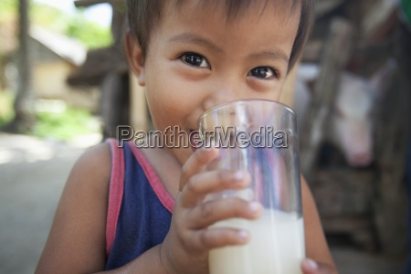a young boy drinks milk outdoors