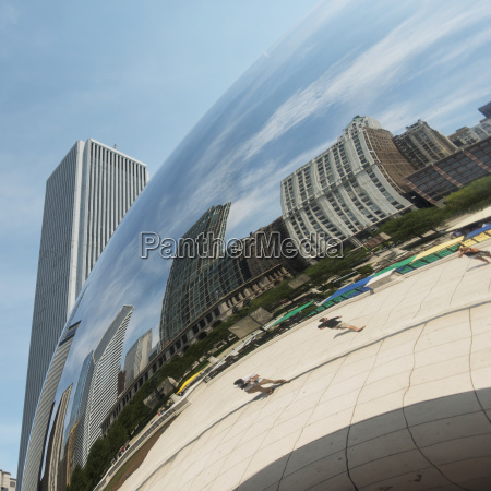 buildings and pedestrians reflected in a