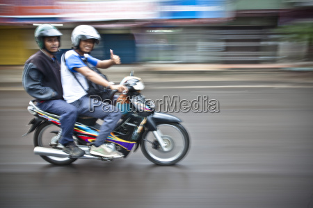 two young men ride a motorbike