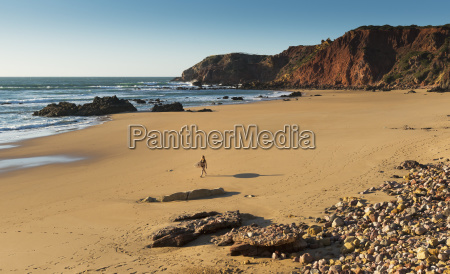 portugal algarve distant view of surfer