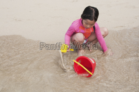 a child plays with a pail