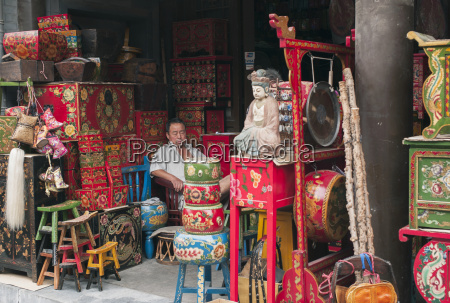 a vendor sits beside the colourful