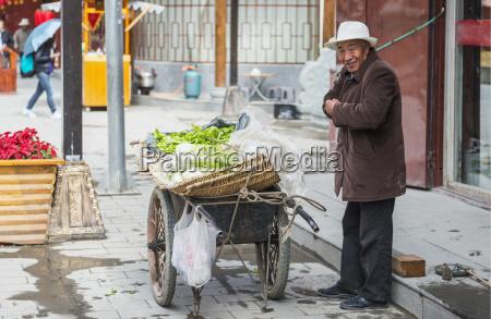 alter mann verkauft gemuese auf der