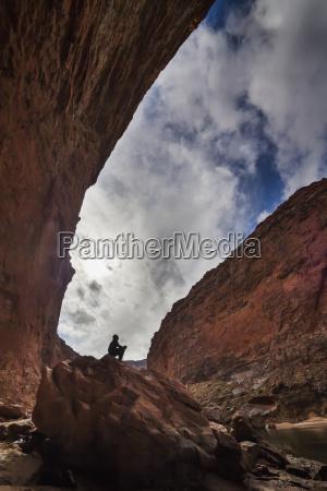 man sits on a rock near