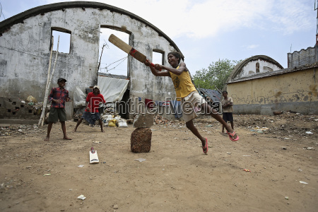 group of boys play cricket close