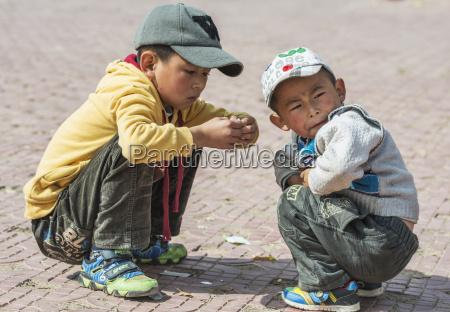 tibetan children are playing near buddhist