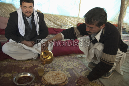 afghan man pouring tea at a