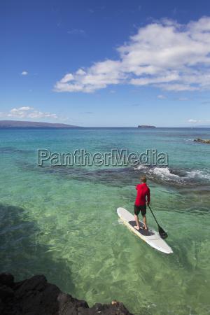 man stand up paddleboarding makena maui