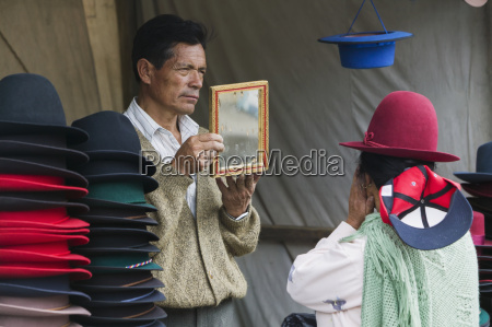 a woman tries a hat on