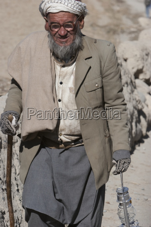 old afghan man holding a lamp