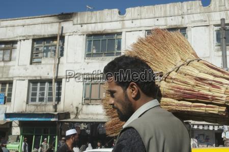 afghan man carrying brooms in kabul