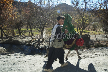 afghan boy walking next to a