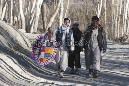 afghan man and boys carrying a