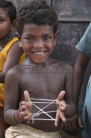 a child plays cats cradle with