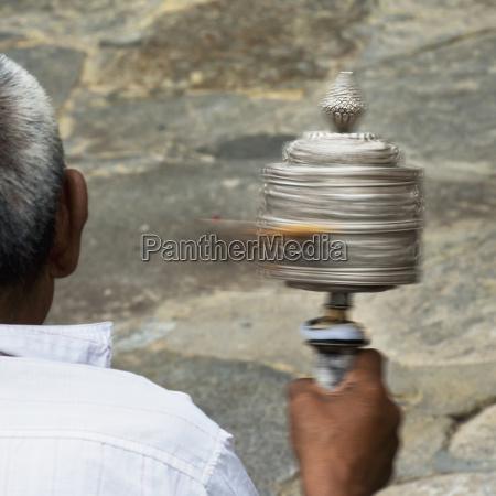 man holding prayer wheel tibet xizang