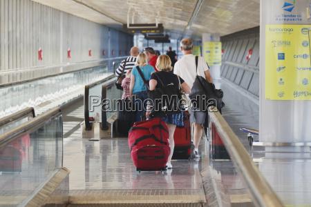 touristen mit gepaeck fuer die abflughlounge