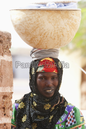 woman carrying a calabash on her