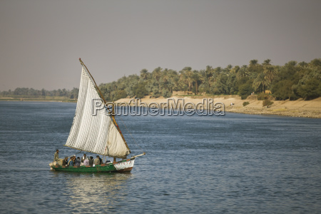 people in an old felucca sailing