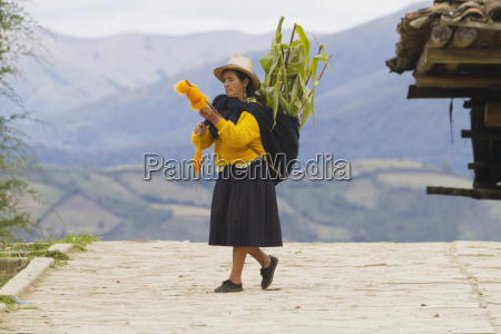 woman carrying corn and spinning wool
