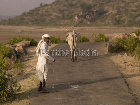 senior man walking along rural road