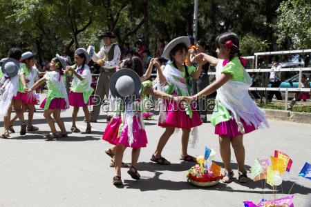 girls dancing around a festive basket