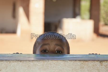 boy peeking through a window in