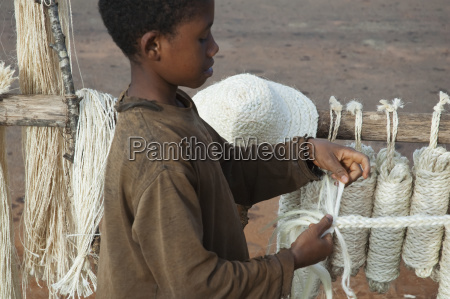 boy making sisal rope along the