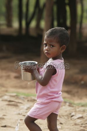 a young girl carries a pot