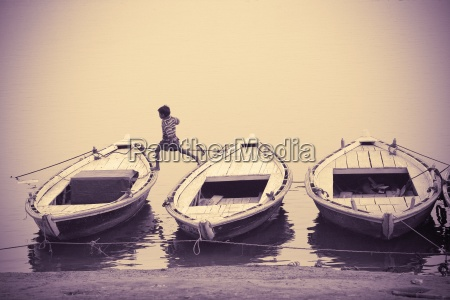 boy jumping along moored boats varanasi