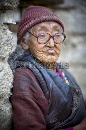 local woman sitting outside monastery lamayuru