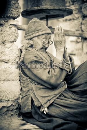 local woman sitting outside monastery praying