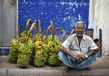 man sitting in front of fruit
