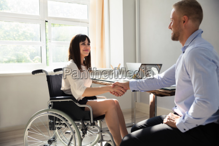 disabled businesswoman shaking hand with her