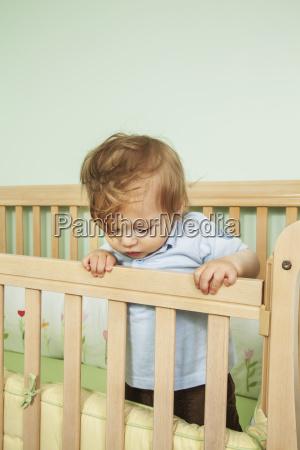 baby in seiner krippe blickend ueber