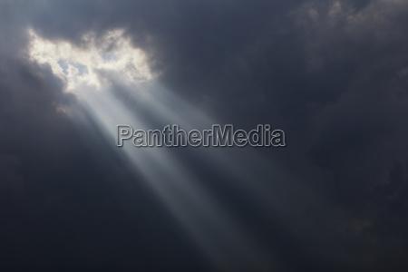 sunlight breaking through dark storm clouds