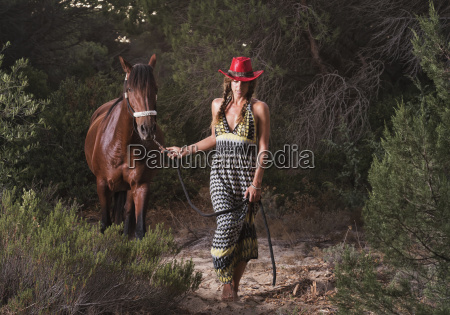 a woman leading her horse over