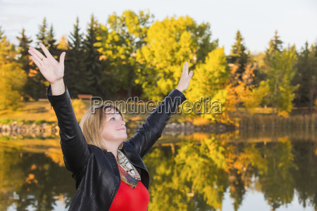 mature woman with arms raised in