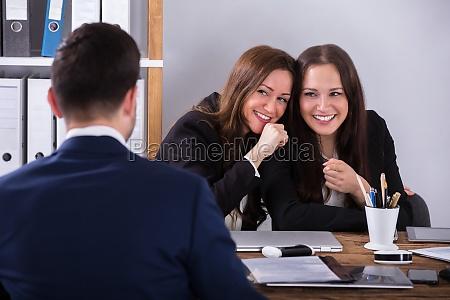 zwei geschaeftsfrau klatschuebert ueber maennliche kollegin