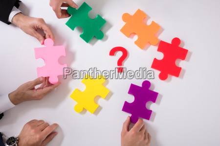 group of businesspeople holding jigsaw puzzle