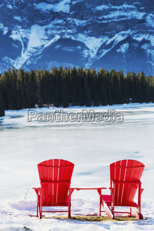 two red chairs on snow covered