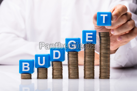 person placing cubic blocks with budget