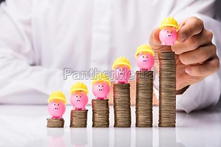 hand placing piggybank with yellow hardhat