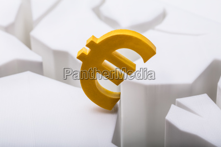 euro waehrungssymbol auf geknackter weisser oberflaeche